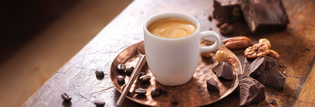 Drank fotografie van een kopje koffie met koffiebonen, chocolade en walnoten gemaakt door Studio_m Fotografie Amsterdam